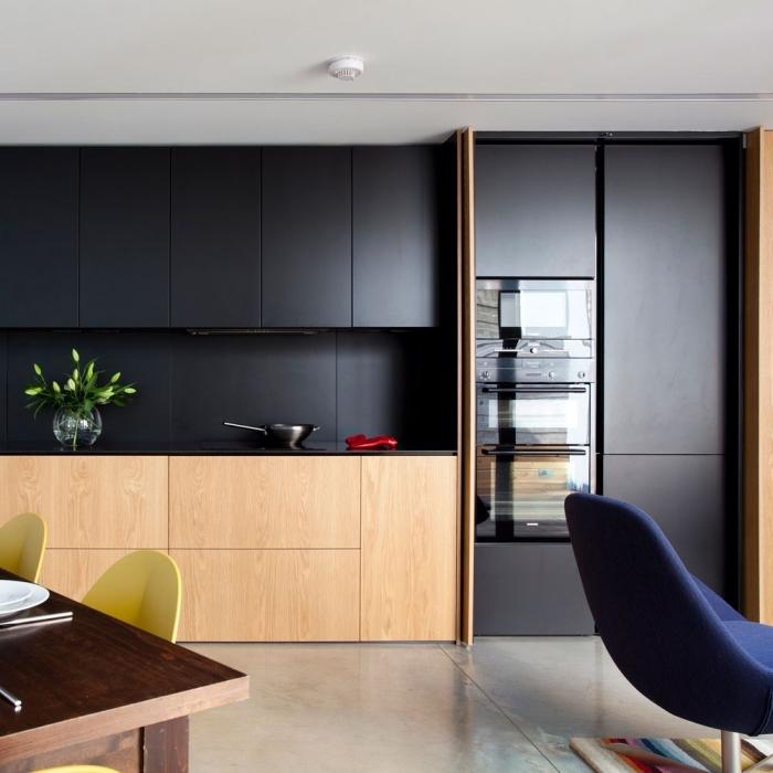 décoration cuisine moderne en noir et bois, meubles haut de cuisine en noir mate, rangement fermé sans poignée