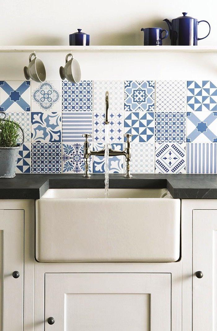 des carreaux de ciment patchwork en nuances de bleu posés en crédence, une crédence lumineuse qui apporte une touche rustique à la cuisine blanche