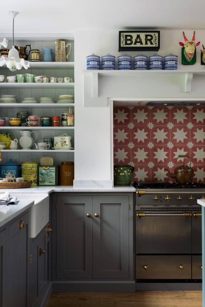 carrelage imitation carreaux de ciment à motifs étoiles stylisées en couleur terre de sienne qui recouvre le fond de hotte, crédence effet carreaux de ciment qui dynamise le décor gris et blanc de la cuisine rustique chic