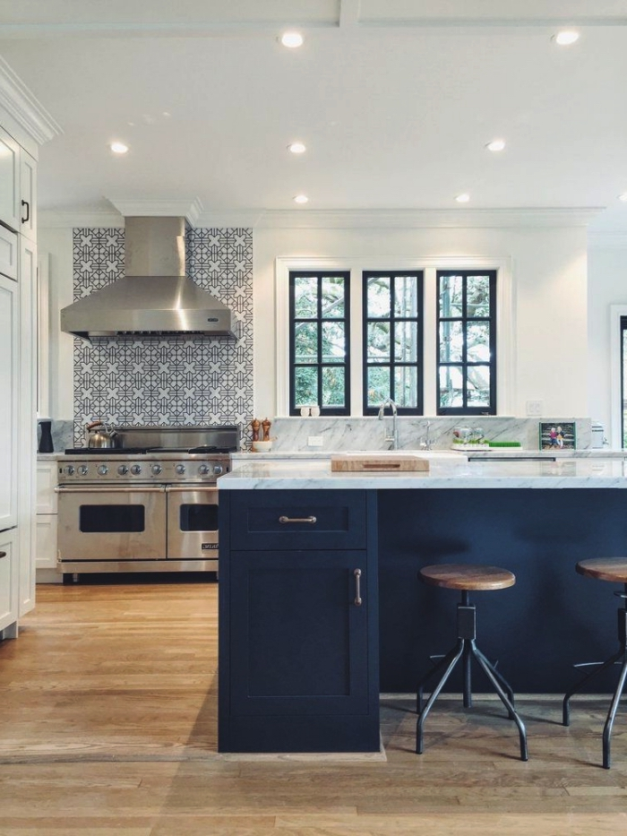 un fond de hotte effet carreaux de ciment adhesif à motifs floraux stylisés en gris clair adopté avec succès dans une cuisine élégante en blanc, bleu et marbre