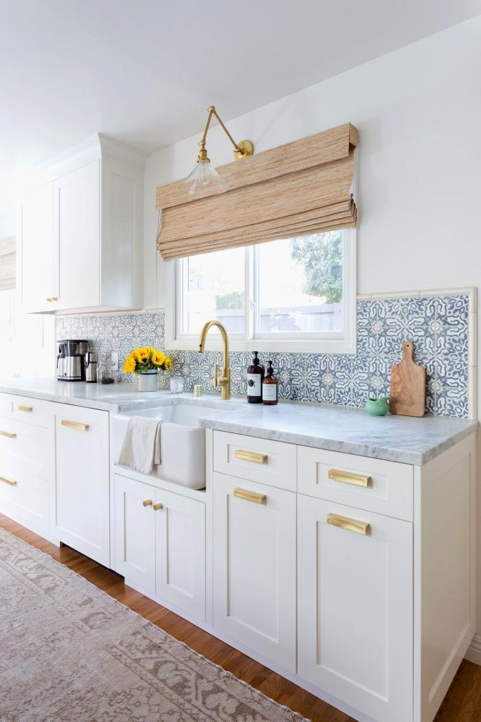 une credence carreaux de ciment lumineuse aux motifs anciens floraux en bleu clair dans une cuisine blanche aux accents laiton