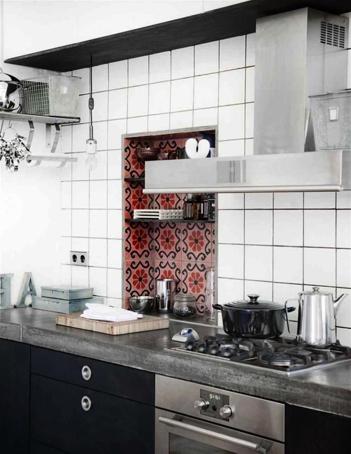une niche murale mise en valeur par des carreaux de ciment marocains en nuances de rose qui apporte du peps à la cuisine industrielle en noir et blanc, un carrelage imitation carreaux de ciment