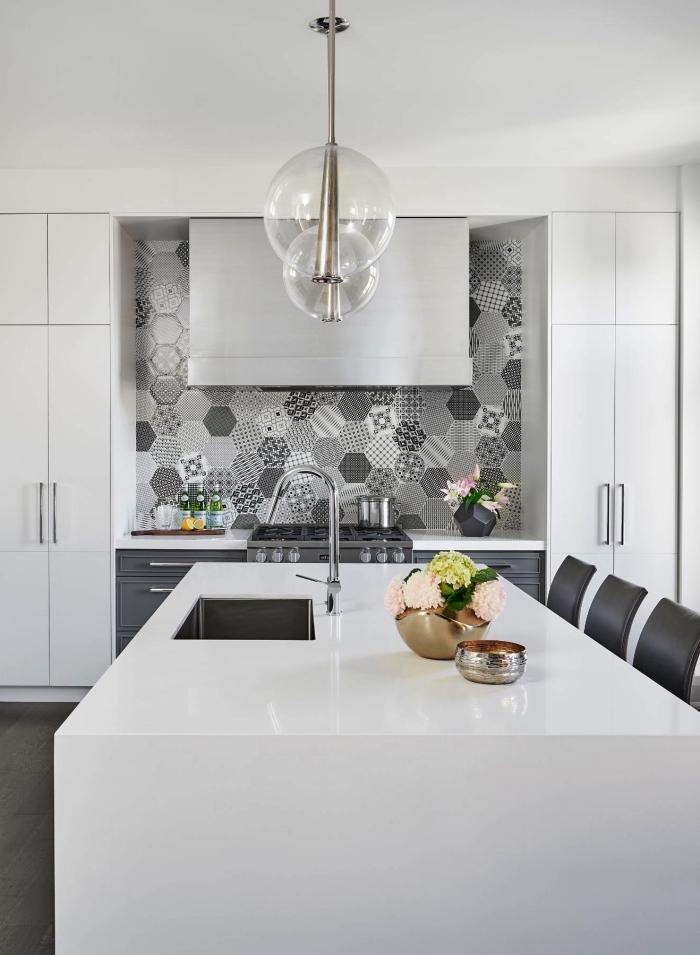 une credence carreaux de ciment hexagonaux de style patchwork en gris clair qui apporte une touche d'élégance dans la cuisine monochrome blanche