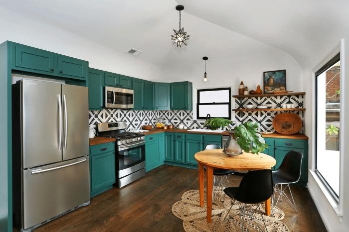 credence carreaux ciment graphiques en noir et blanc qui contrastent joliment avec les meubles de cuisine bleu canard, une cuisine de style bohème chic équipée d'une crédence graphique