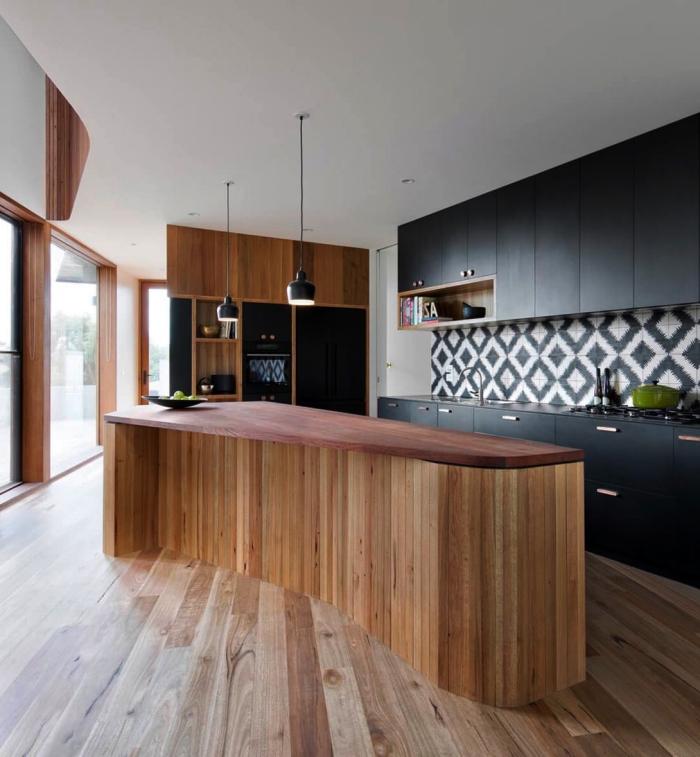 une crédence cuisine carreaux de ciment graphique en noir et blanc qui sert de trait d'union entre le noir mat et le bois des meubles de cuisine