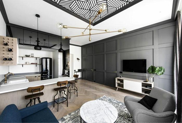 cuisine en gris et blanc, kitchenette pour stufio, ilot de cuisine, chaises en bois, table ronde marbrée, tapis gris, panneaux muraux gris