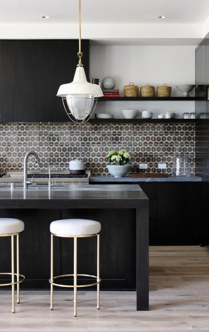 une crédence imitation carreaux de ciment à motifs hexagonaux gris taupe qui apporte une touche d'élégance à la cuisine noire