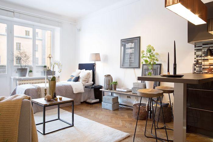 murs blancs, lit gris et blanc, parquet bois clair, cuisine ouverte sur espace nuit et salon deux en un, tapis blanc, art cadres noir et blanc