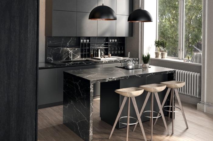 idée crédence à design marbre noir, aménagement cuisine moderne avec îlot central marbre noir, type d'éclairage au-dessus d'îlot