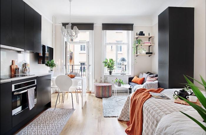 idée d aménagement cuisine petite espace couleur noire en face d un coin chambre à coucher, armoire noire, murs blancs, petit salon en canapé gris, table basse pliante blanche