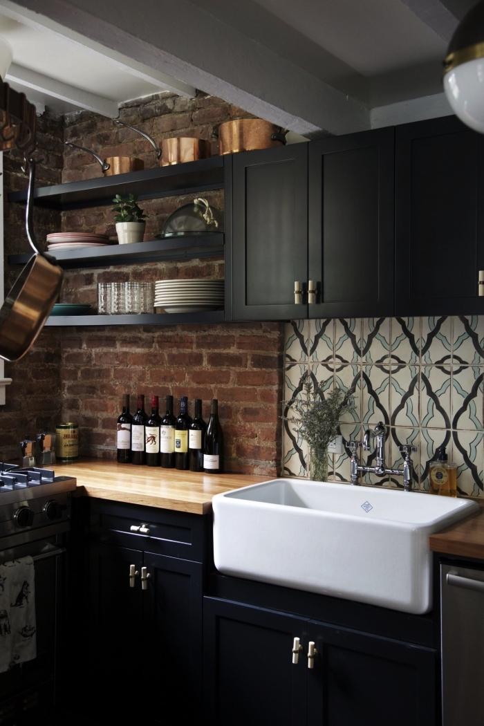une credence carreau de ciment graphique et vintage en beige et bleu qui apporte une jolie touche déco dans la cuisine en bois et noir de style loft industriel