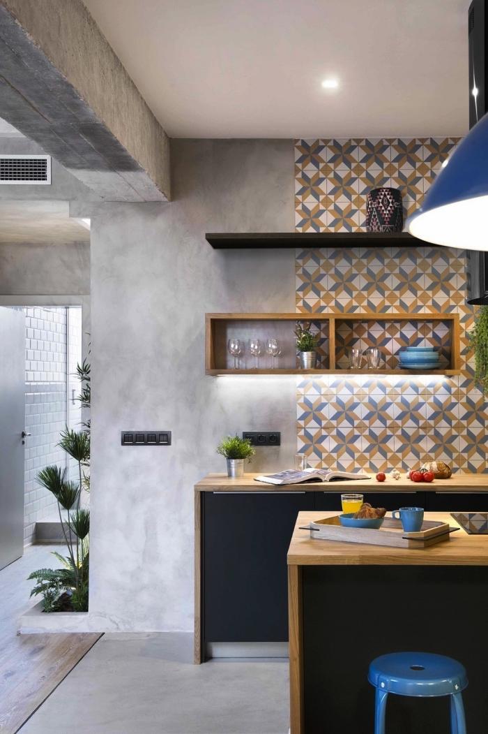 des carreaux de ciment adhesif qui recouvre une partie du mur jusqu'au plafond, en contraste avec les murs effet béton, des meubles de cuisine bois et noir mat