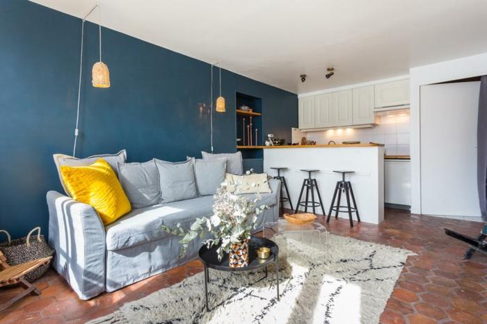 sofa gris, tapis berbère, coussin jaune, peinture murale bleue, lampes suspendues, cuisine petit espace avec îlot, sol en tomettes rouges