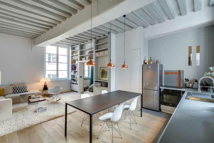 grand salon avec table de repas et petite cuisine en L, coin cuisine et chambre à coucher, tapis couleur crème, lampes suspendues cuivrées