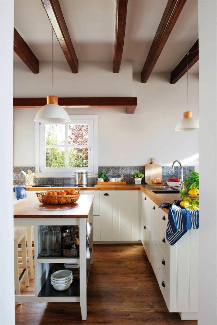 une fine crédence imitation carreaux de ciment aux motifs anciens en bleu dans la cuisine de style campagne en blanc et bois