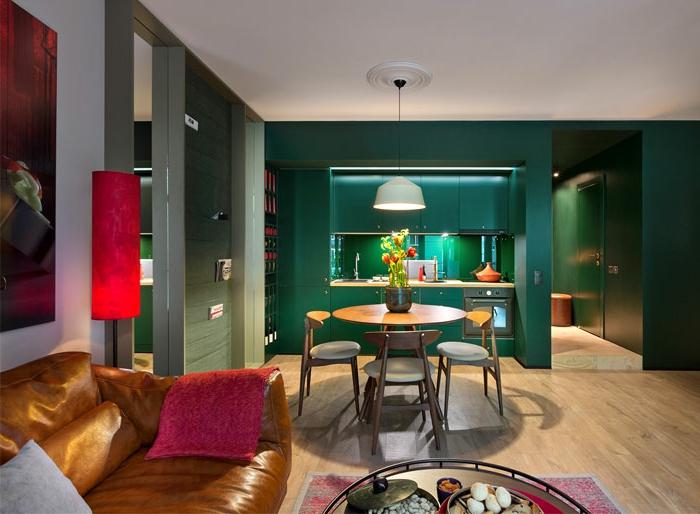 salon avec cuisine, studio espace ouvertn table ronde, chaises, table basse de salon, coin cuisine, meuble kitchenette vert