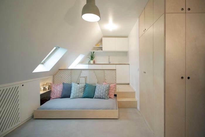 design minimaliste de studio avec cuisine sous comble en blanc, lit cocooning en bois avec coussins colorés et armoire bois, aménagement de studio