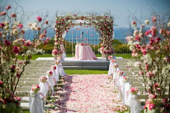 mariage en blanc et rose, cérémonie à l'extérieur, pétales de roses parsemées au sol, banquettes blanches