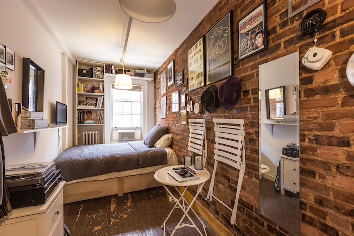 style deco indistrielle avec mur de briques, lit entr deux murs, chaises pliantes installées sur mur, niche murale bibliothèque, parquet retro chic