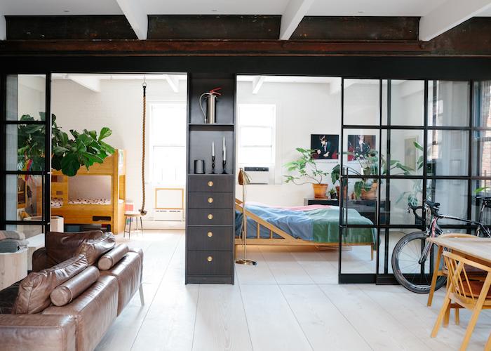 chambre za coucher adulte et chambre enfant séparés par une verrière industrielle noire d une salle à manger et salon avec canapé en cuir, plantes pour deco zen