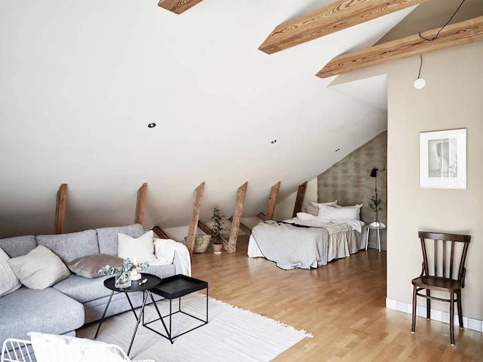 poutres apparentes dans un espace sous comble avec lit sous pente et canapé gris, tables gigognes couleur noire, murs gris et blanc