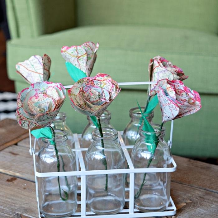 une rose en papier découpée dans une carte routière récupérée, des roses en papiers posés dans des vases soliflores vintage décorés avec des