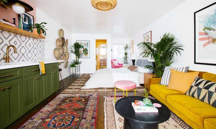canapé jaune moutarde en face d une cuisine vert olive avec étagère bois ouverte, tapis oriental, lit cocooning, deco murale artistique, aménager un studio boheme chic exotique