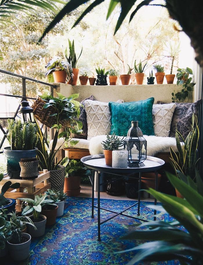 deco boheme chic de balcon cosy avec canapé décoré de plaid et coussins colorés, tapis oriental, petit jardin exterieur de plantes grasses, table basse ronde