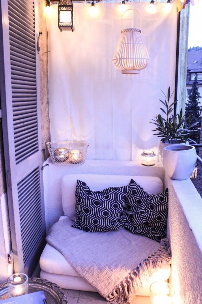 idee d aménagement petit balcon avec petit fauteuil par sol décoré de coussins noir et blanc et couverture grise, deco de bougeoirs et lanterne suspendue