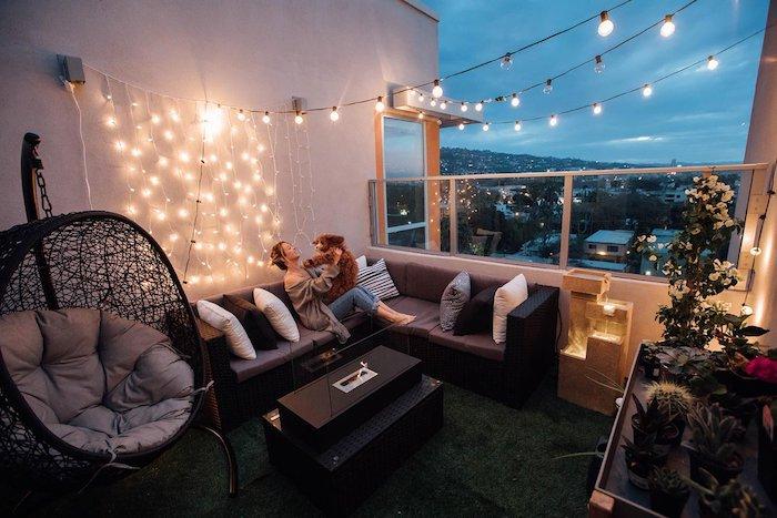 deco hygge de balcon spacieux avec balancelle, cananpé d angle noir avec coussin d assise gris et deco de guirlande lumineuse, revetement balcon d herbe artificielle, plantes decoratives