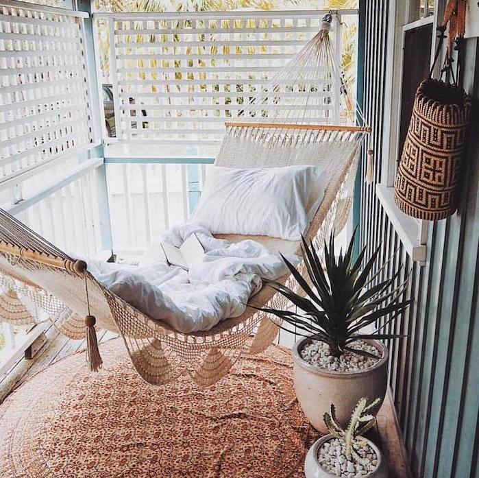 idee deco hygge de balcon avec brise vue artificielle, hamac d exterieur style hippie chic, coin de lecture cocoon, tapis rond oriental, plantes en pots de terre cuite