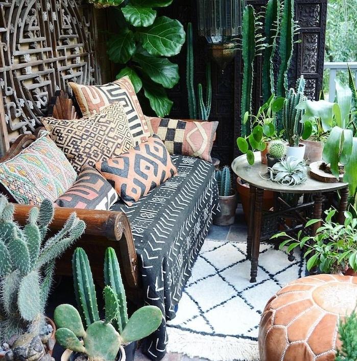 idee de deco balcon avec canapé et coussins decoratifs motif exotique, plantes grasses d extérieur, deco boheme style jungle urbain, pouf marron