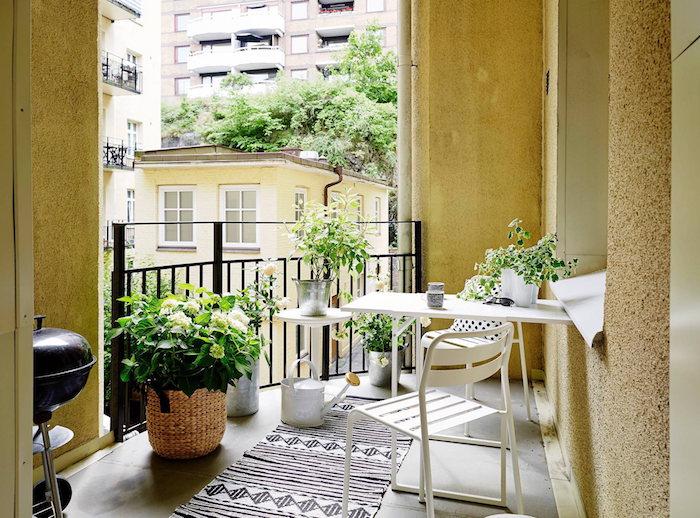 mini balcon en plein ville de paris, table et chaises en metal blanches, tapis noir et blanc, plantes vertes de balcon, garde corps metal noir