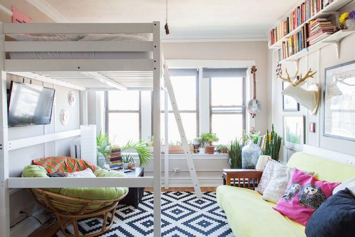 lit en hauteur avec un fauteuil cocooning abrité en dessius, tapis noir et blanc, canapé bois et vert, murs blancs, plantes vertes et étagères en hauteur