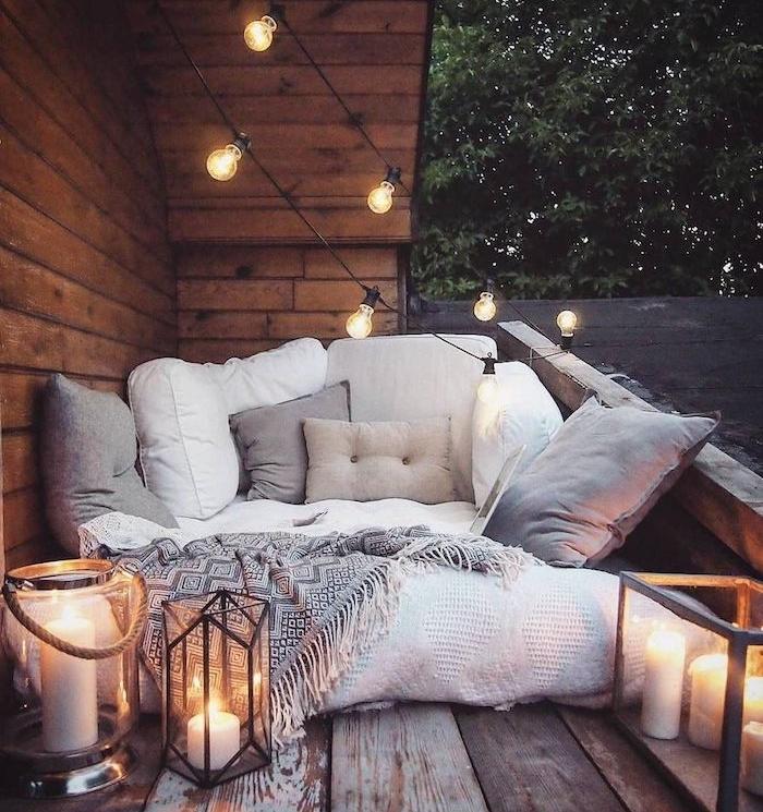 idee de decoration balcon avec matelas couvert de plaids et couvertures moelleuses, coussins decoratifs gris, guirlande d ampoules electriques, lanternes à bougies