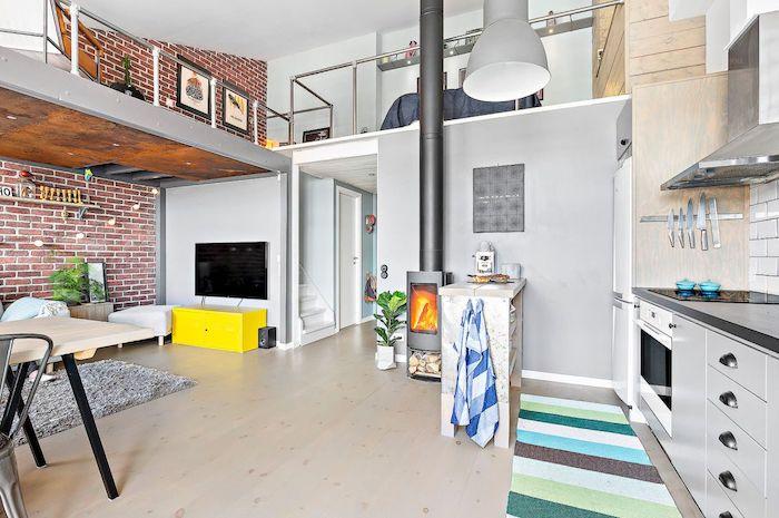 idee deco mezzanine avec espace chambre à coucher et espace détente, kitchenette pour studio grise, cheminée moderne et salon avec mur de briques et mobilier moderne