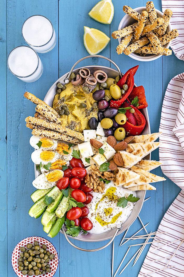Que mettre au centre de la table, mezzé froid avec houmous et concombres, poivres et olives, pan arabe en morceaux