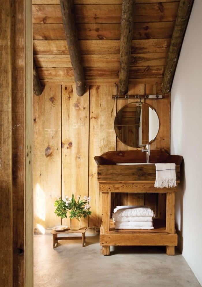 aménagement petite salle de bain sous pente, décoration rustique avec lambris et poutres bois apparentes, vasque bois brut