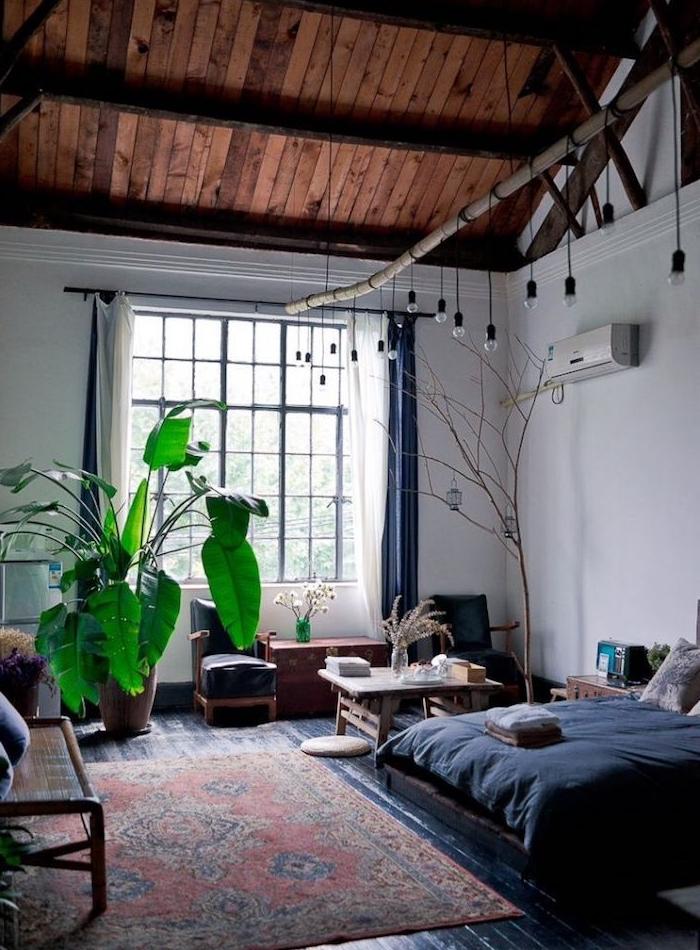 lit avec linge de lit gris, murs blancs, toiture ossature apparente bois, tapis oriental et espace salon à coté, éclairage ampoules suspendues