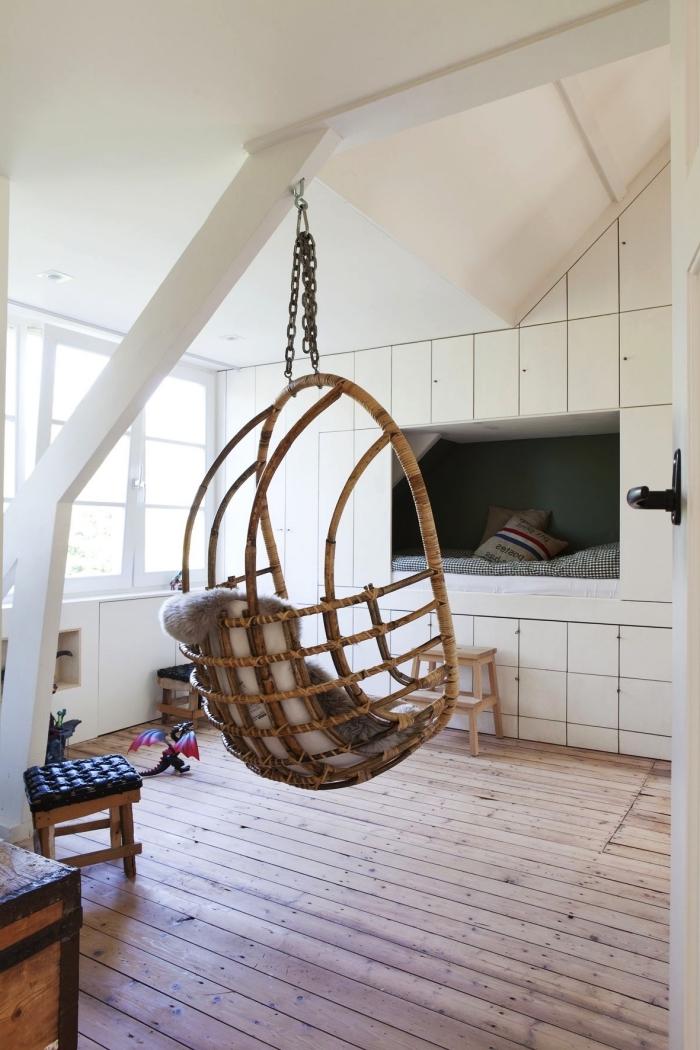 une chambre d'enfant scandinave avec fauteuil suspendu, meuble sous pente encastré au mur avec niche murale façon lit cabane