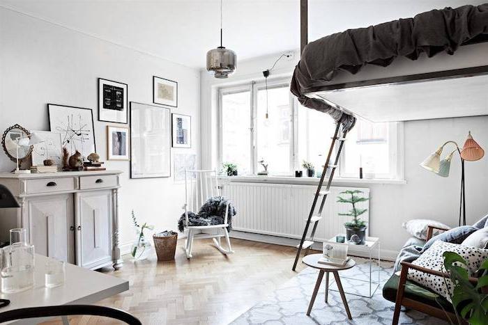 lit en hauteur dans une chambre à coucher aux murs blancs, commode gris clair, deco mur de cadres, parquet bois clair, salon sous lit, canapé bois et vert, tables bases décoratives