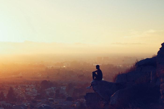Homme assise sur un rocher avec belle vue au coucher de soleil, beau paysage urbain, image à utiliser pour fond d'écran libre de droit