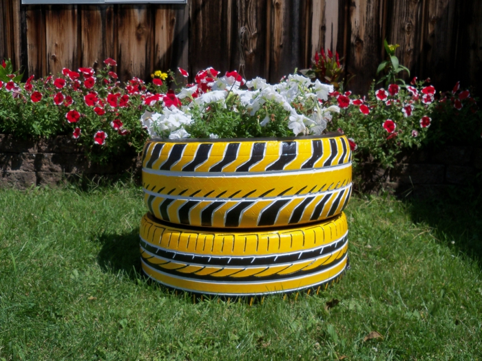 pneus peints jaunes, pelouse, pétunias plantés, clôture en bois, herbe verte, decor jardin