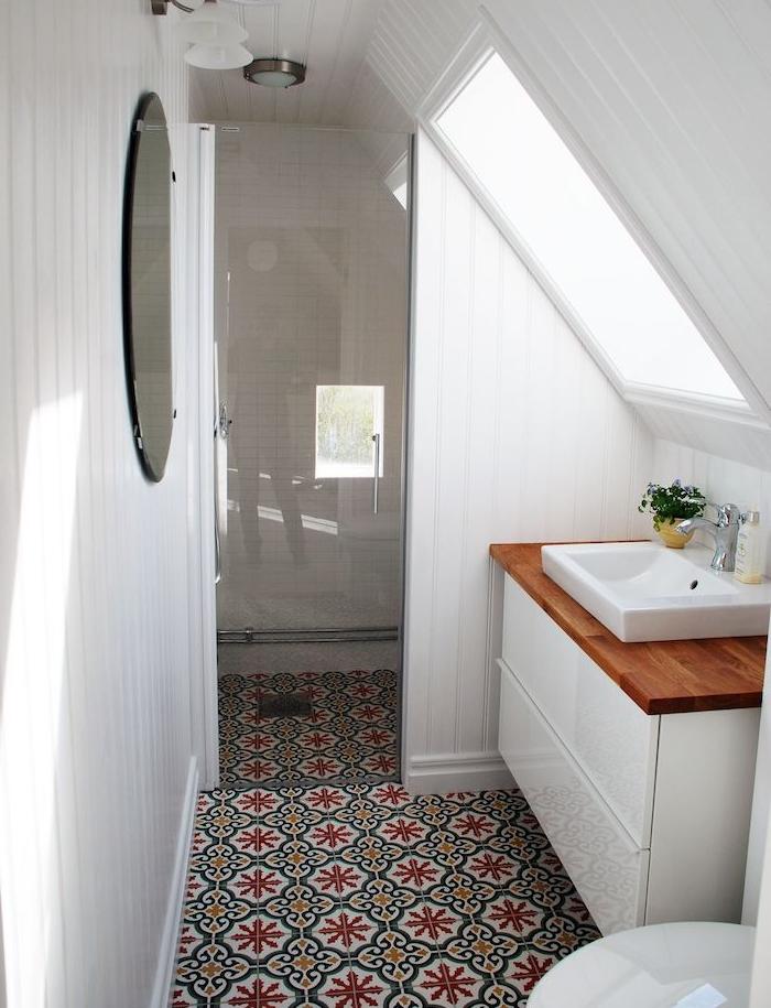 carrelage mosaique à motifs floraux dans salle de bain avec meuble sous vasque blanc avec plan de travail bois, wc blanc, murs lambris blanc, miroir rond, douche à paroi vitré