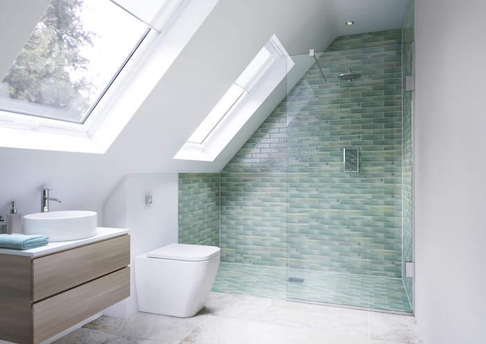 douche en carrelage vert avec un paroi vitré, sol en carrelage gris et blanc, meuble sous vasque en bois clair, wc blanc