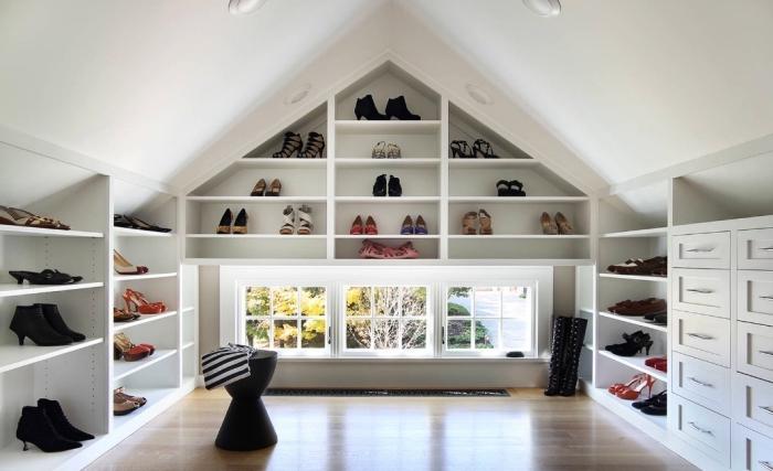 un dressing sous pente dédié aux chaussures avec des étagères sur mesure intégrées au mur