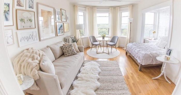 salon gris et blanc avec chambre à coucher design cocooning à coté, canapé grand gris perle. table avec chaises minimalistes