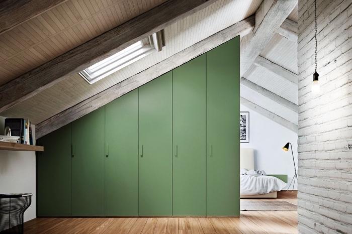 une armoire sous pente verte qui sépare l'espace de la chambre à coucher mansardée en deux