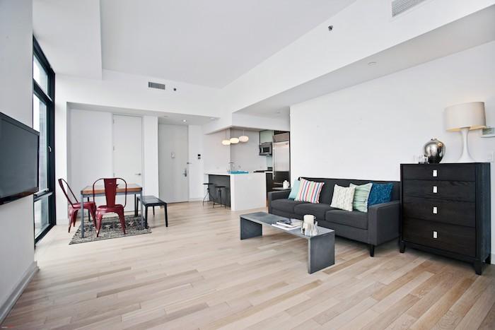 canapé gris et table basse effet béton, deco salon ouvert sur cuisine gris et blanc et salle à manger à chaises et table industrielles
