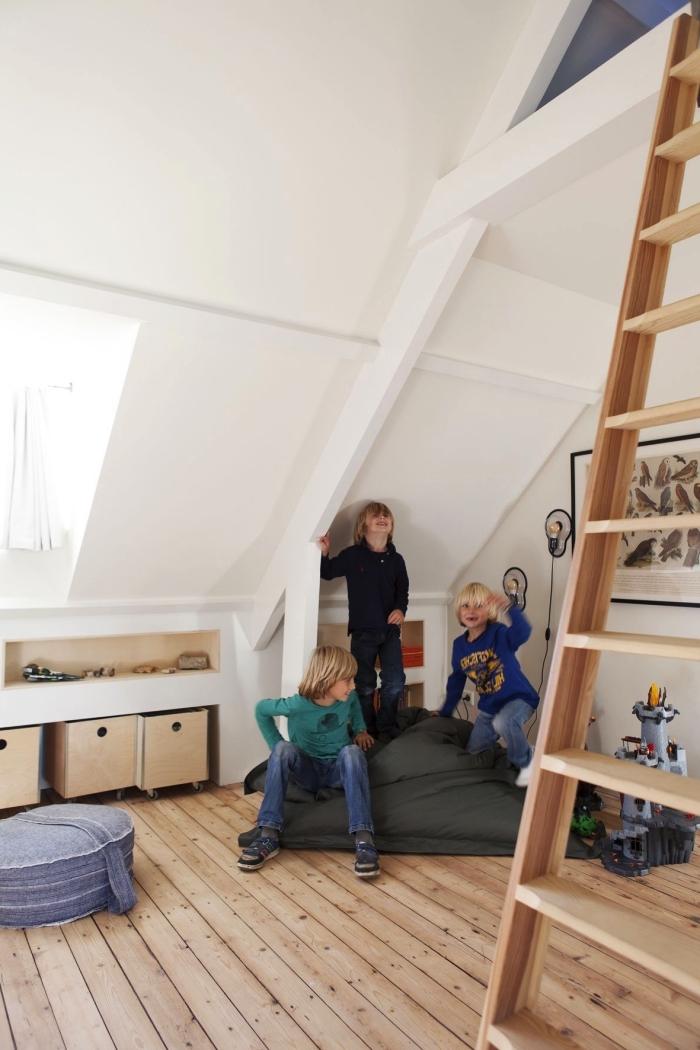 une chambre d'enfant mansardée de style scandinave avec etagere sous pente gain de place et un lit cabane aménagé sous les combles, espace de jeu dans les combles